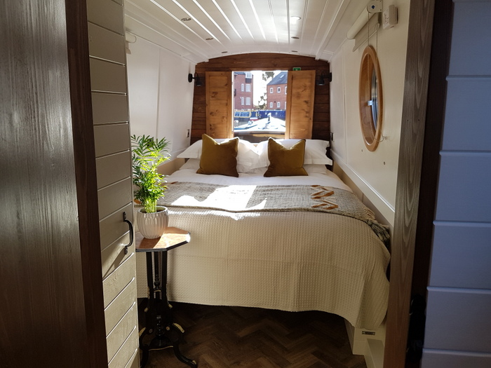 King sized bed in the front of Boutique Narrowboat Woodland Grayling